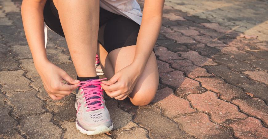 Kvindelig løbere binder skoerne